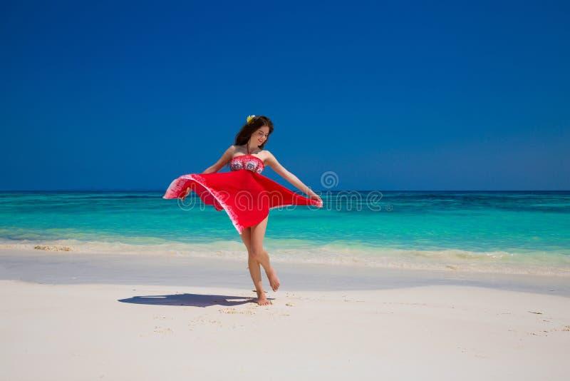Härlig lycklig kvinnadans som tycker om på den exotiska stranden i sommar royaltyfri fotografi