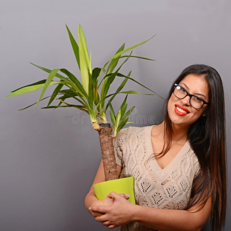 Härlig lycklig kvinnainnehavväxt i vas mot grå bakgrund royaltyfria foton