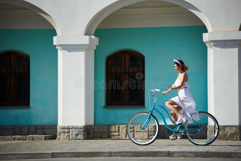 Härlig lycklig kvinnaridningcykel i staden arkivfoton