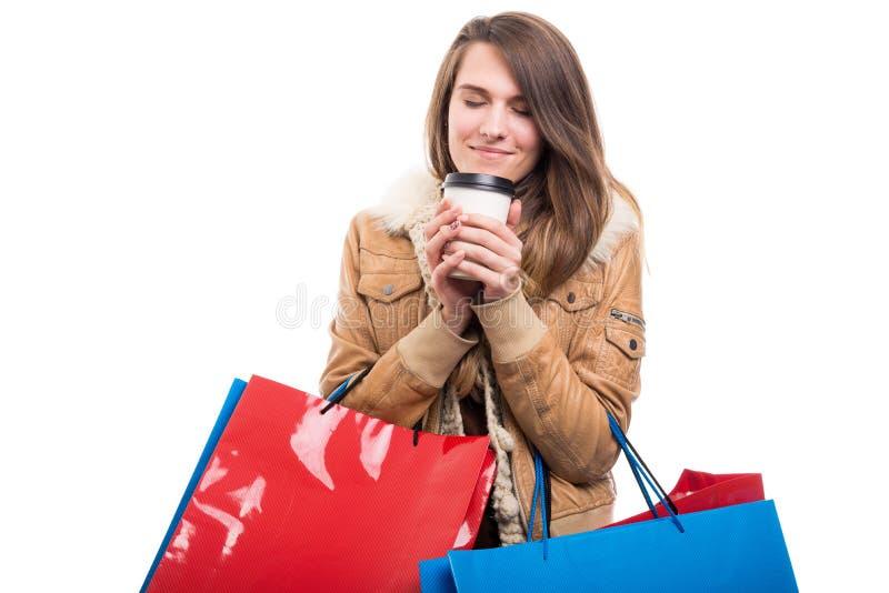 Härlig lycklig kvinnlig som tycker om kaffe, når att ha shoppat fotografering för bildbyråer