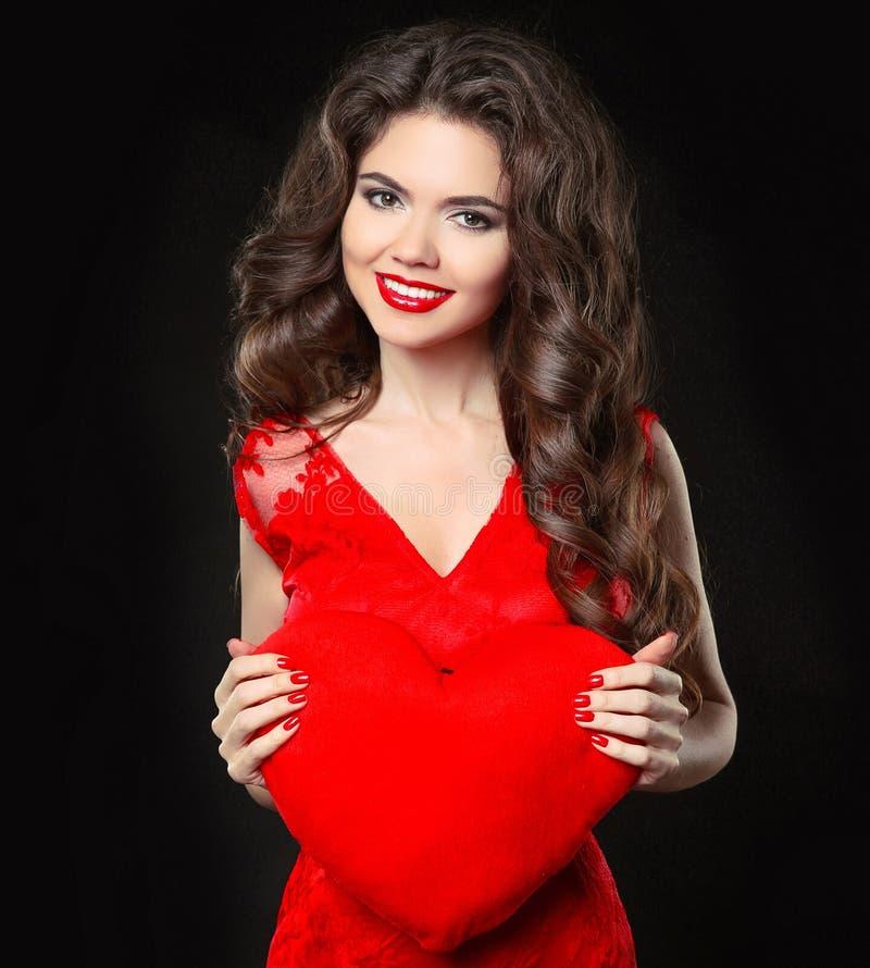 Härlig lycklig le flicka i hållande valentin för röd klänning hjärta Brunett med den långa lockiga frisyren och röda kanter som i royaltyfri bild