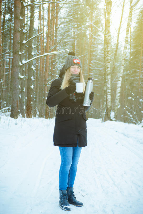 Härlig lycklig le kvinna med en kopp av vintern på gatan varm drink för leendenjutningflicka utomhus fotografering för bildbyråer