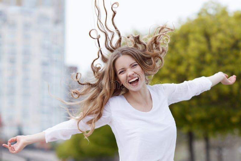 Härlig lycklig le kvinna med hårflyg i sitybakgrunden royaltyfri bild