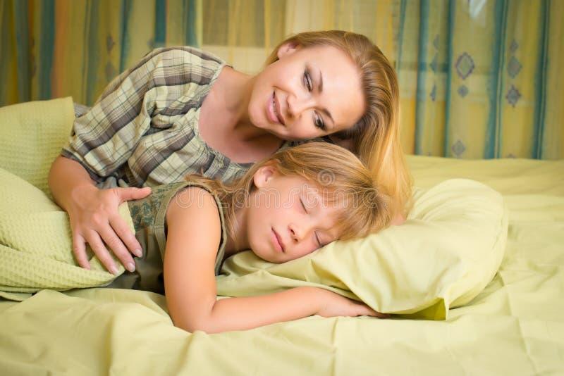 Härlig lycklig le moder som omfamnar hennes gulliga dotter som sover i säng arkivbilder