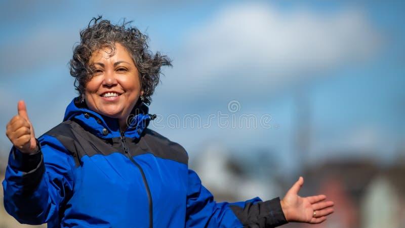 Härlig lycklig mogen mexikansk kvinna med hennes hår som rufsas till av vinden med ett blått omslag royaltyfri bild