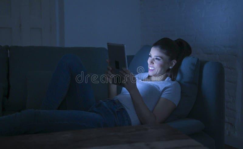 härlig lycklig och avkopplad latinsk kvinna30-tal som sent ligger på hem- natt för soffa - genom att använda digitalt hålla ögone royaltyfria bilder