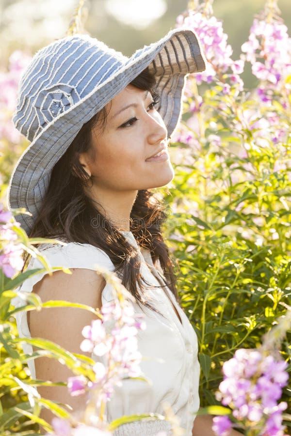 Härlig, lycklig, sund, sinnlig, sexig ung asiatisk kvinna som tycker om sommarsolljus i en blommaträdgård Hon bär en solhatt royaltyfri foto