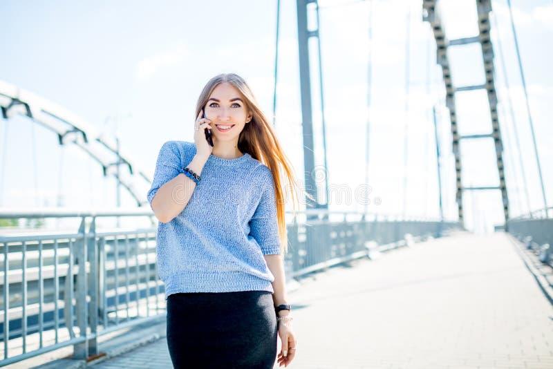 Härlig lycklig ung affärskvinna som använder mobiltelefonen på stadsgatan royaltyfri foto