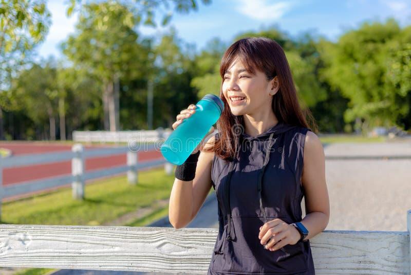 Härlig lycklig ung asiatisk kvinna som dricker hennes vatten i morgonen på ett rinnande spår, innan att starta hennes övning arkivfoton
