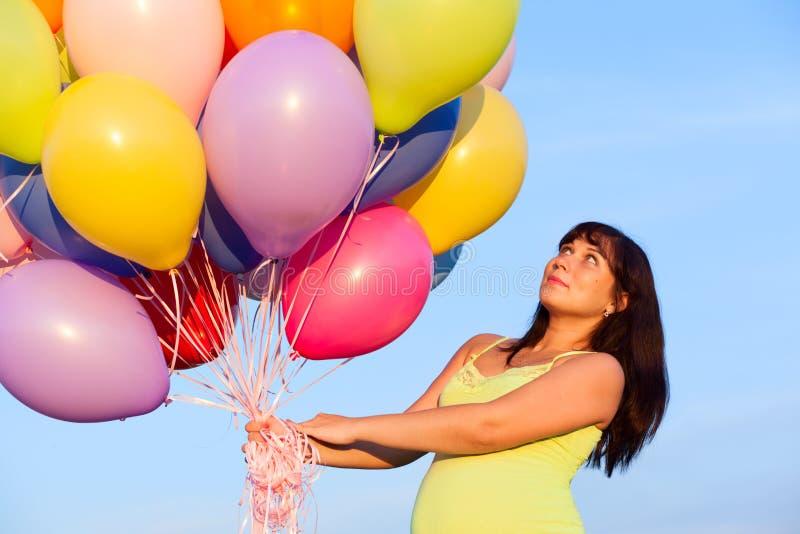 Härlig lycklig ung gravid kvinnaflicka utomhus med ballonger royaltyfri foto