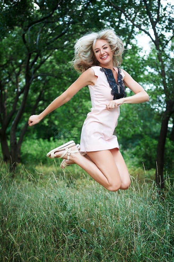 Härlig lycklig ung kvinna som högt hoppar i luft i parkera royaltyfri foto