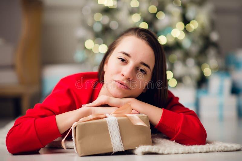 Härlig lycklig ung kvinna som ligger på golvet som rymmer en julklapp arkivfoton