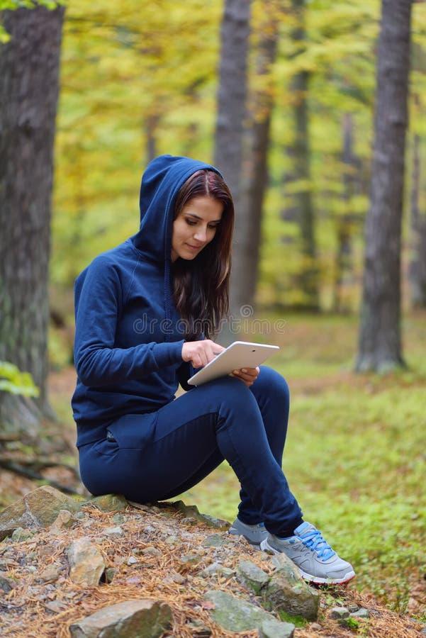 Härlig lycklig ung kvinna som surfar rengöringsduken och läsningen på en flik fotografering för bildbyråer