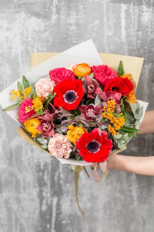 Härlig lyxig bukett av blandade blommor i kvinnahand arbetet av blomsterhandlaren på en blomsterhandel royaltyfria bilder