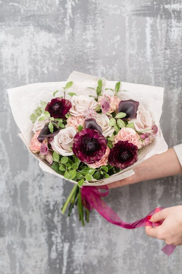 Härlig lyxig bukett av blandade blommor i kvinnahand arbetet av blomsterhandlaren på en blomsterhandel arkivbild