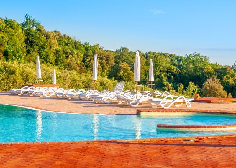 Härlig lyxig simbassäng med ljusa blått vatten, paraplyer och sunbeds i det Tuscan landskapet Aftonsommarsolnedgång royaltyfri fotografi
