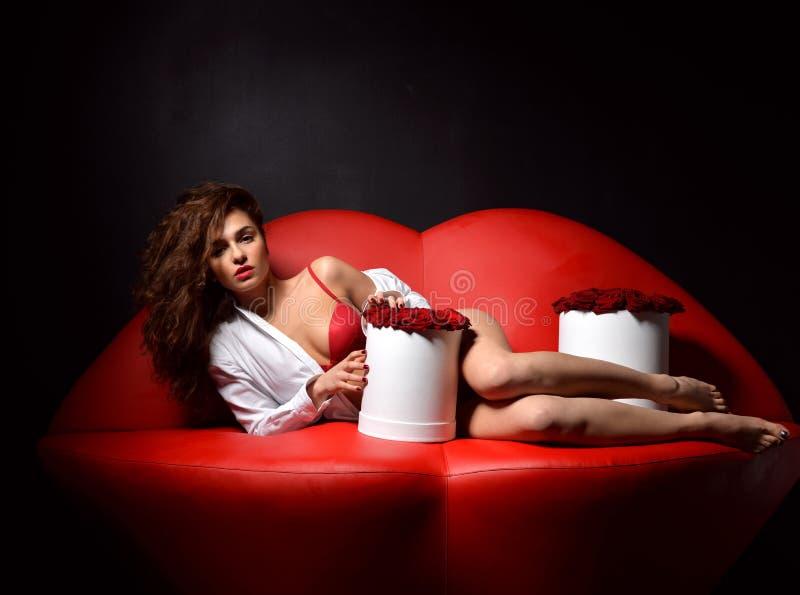Härlig lyxig trendig sexig kvinna som ligger på röd kantsoffa c arkivbilder