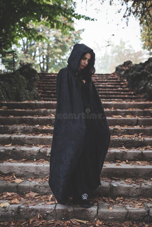 Härlig mörk vampyrkvinna med det svarta ansvaret och huven royaltyfria foton