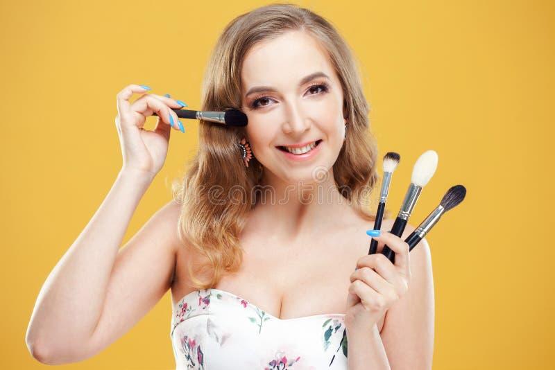 H?rlig makeupkonstn?r f?r ung kvinna med en upps?ttning av yrkesm?ssiga makeupborstar royaltyfria bilder