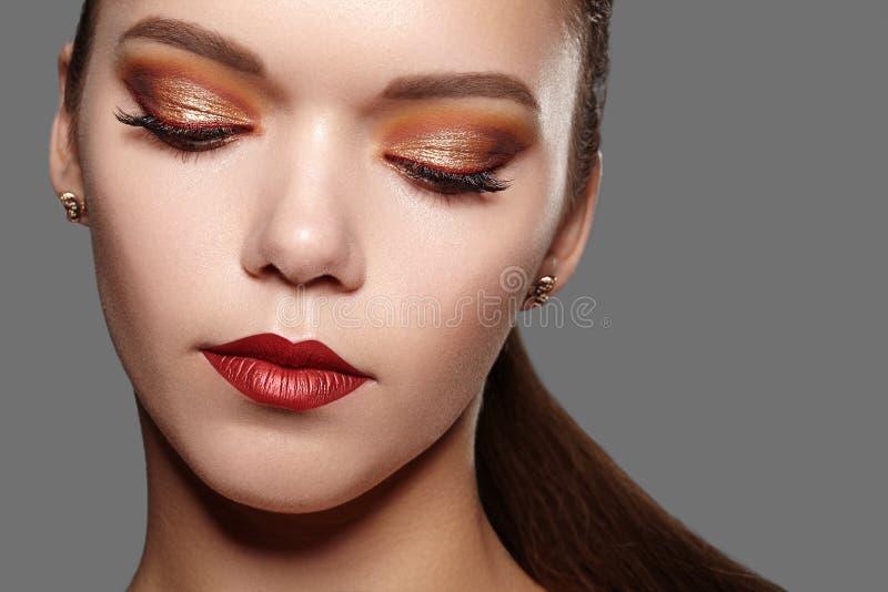 härlig makeupprofessionellkvinna Skiner det guld- ögonsminket för partiet, perfekta ögonbryn, hud Ljus modeblick fotografering för bildbyråer