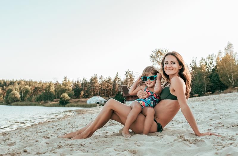 Härlig mamma för ung kvinna som sitter på lakeside med sand, i armarna av en småbarndotter, lyckligt le, familj arkivbild