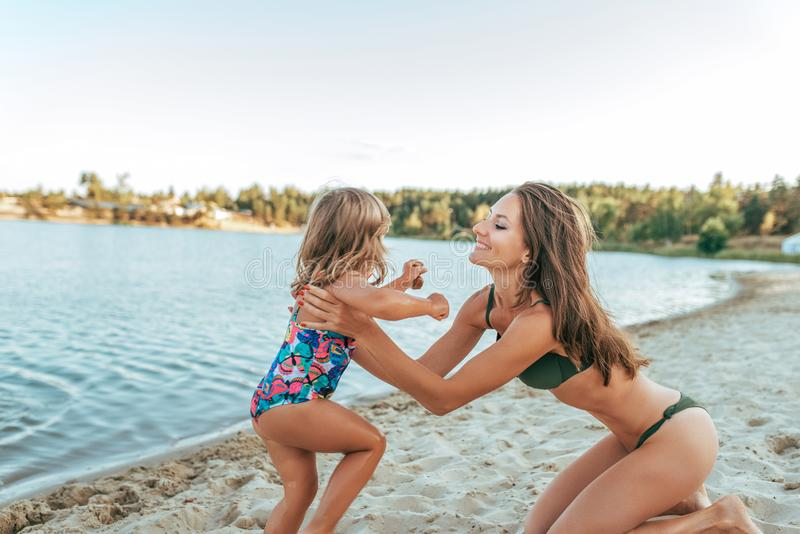 Härlig mamma för ung kvinna som spelar på kusten av sjön med sand som rymmer en småbarndotter, lycklig le familj royaltyfri foto