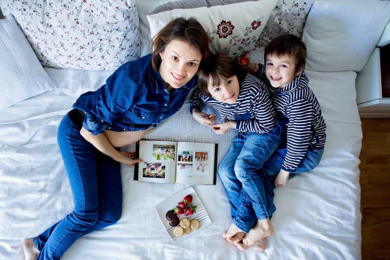 Härlig mamma och två barn, pojkar och att ligga på sängen som äter s royaltyfri bild