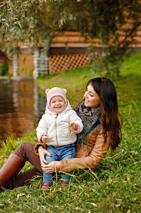 Härlig mammabrunett som rymmer en charmig härlig liten flicka arkivfoto