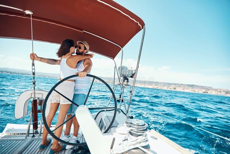 Härlig man och kvinna av vänner som seglar på ett fartyg och att tycka om ljus solig dag royaltyfria bilder