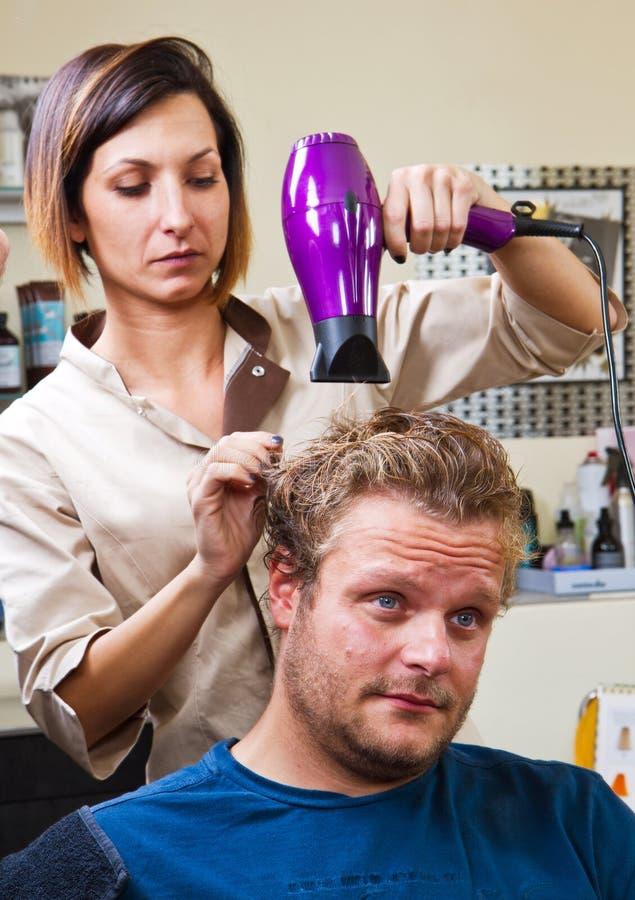 Härlig man på frisörslaget som torkar hans hår royaltyfri foto