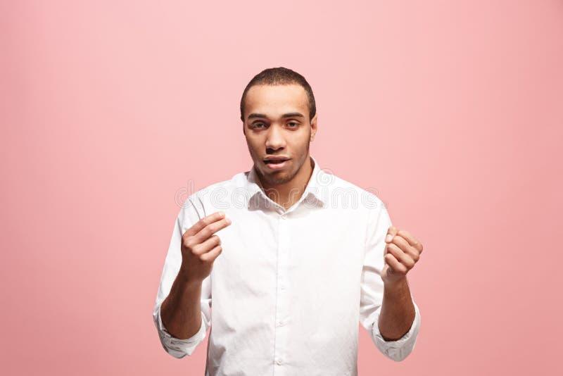 Härlig manlig i halvfigur stående på rosa studiobackgroud Den unga emotionella förvånade mannen royaltyfri bild