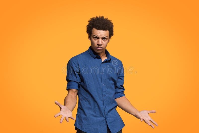 Härlig manlig i halvfigur stående som isoleras på orange studiobackgroud Den unga emotionella afro mannen arkivfoto