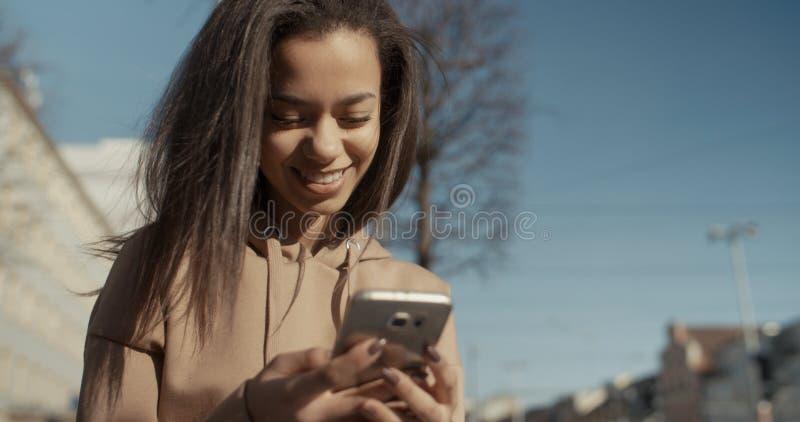Härlig maskinskrivning för ung kvinna på telefonen under solig dag royaltyfria foton