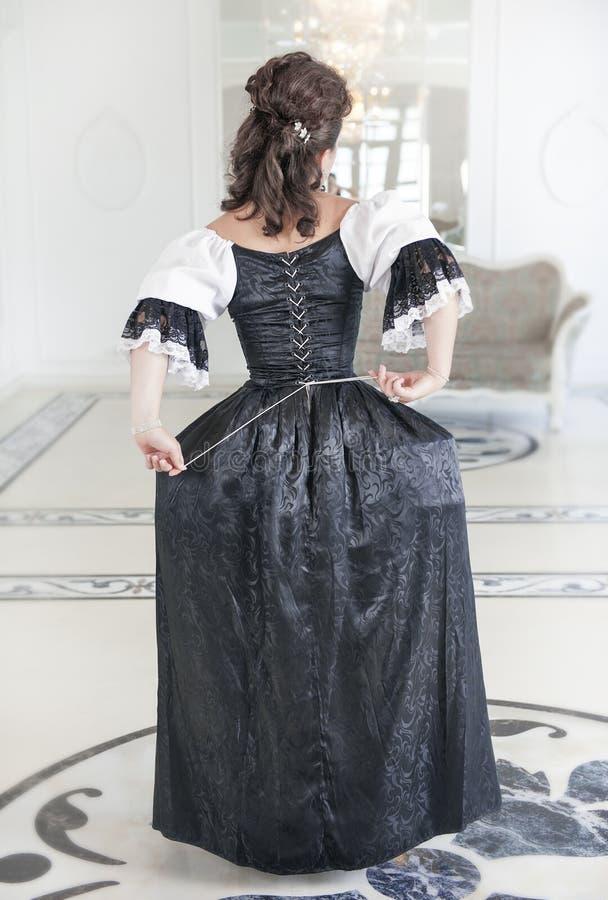 Härlig medeltida kvinna i den långa klänningen, baksida arkivfoto