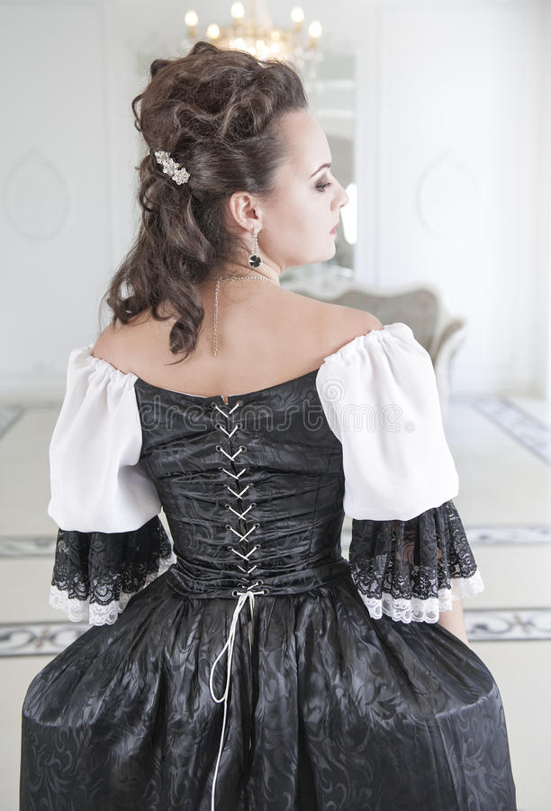 Härlig medeltida kvinna i den svartvita klänningen, baksida arkivbilder