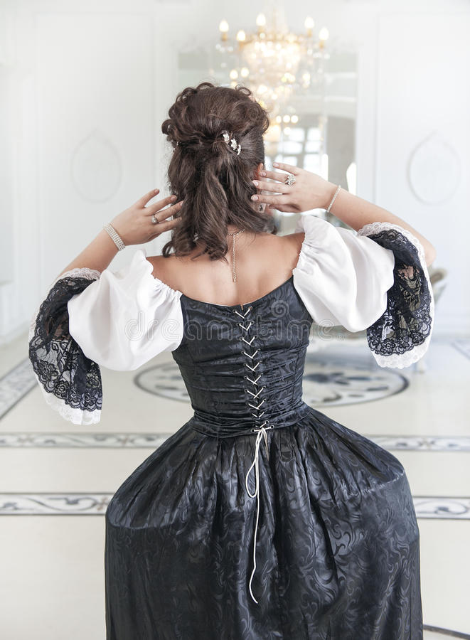 Härlig medeltida kvinna i den svartvita klänningen, baksida arkivfoton