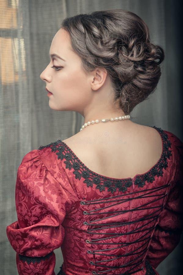 Härlig medeltida kvinna i röd klänning royaltyfri foto