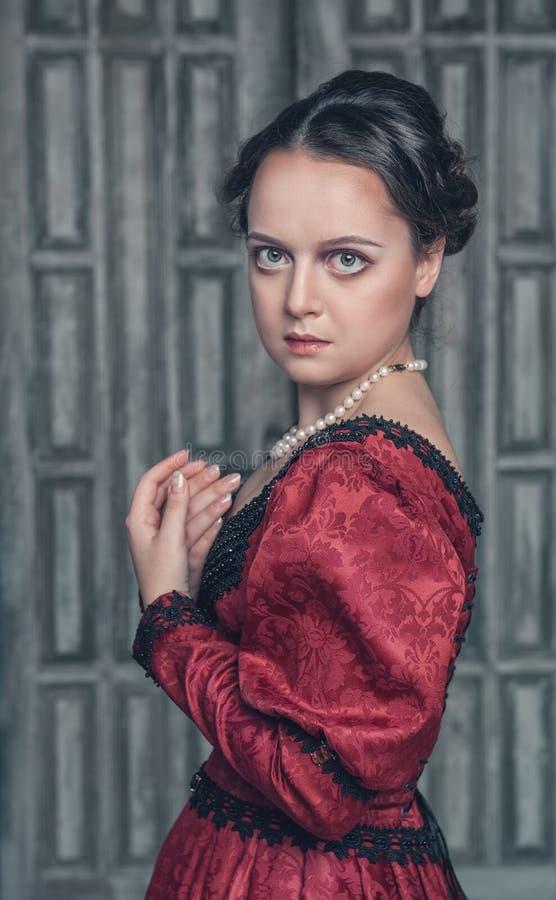 Härlig medeltida kvinna i röd klänning arkivbilder