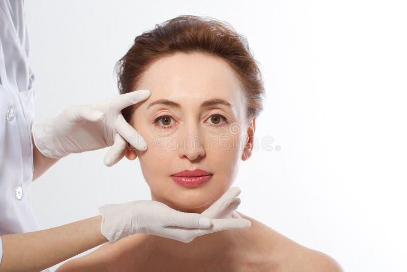 Härlig mellersta ålderkvinna för plastikkirurgi Makroframsida med händer för skrynkla- och doktors` s på vit bakgrund arkivfoto