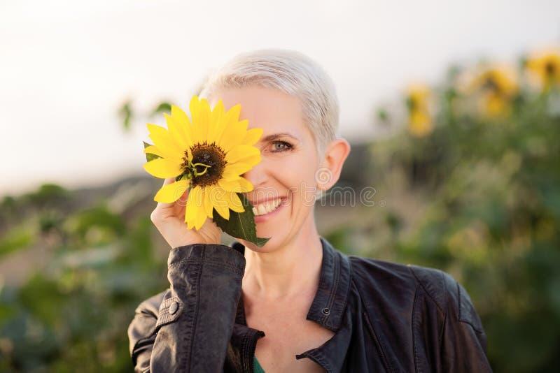Härlig mellersta ålderkvinna i en lantlig fältplats som står utomhus mellan solrosor royaltyfri fotografi