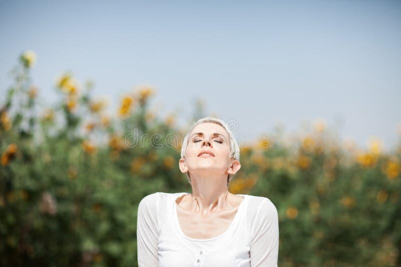 Härlig mellersta ålderkvinna i en lantlig fältplats utomhus med solrosor arkivfoton