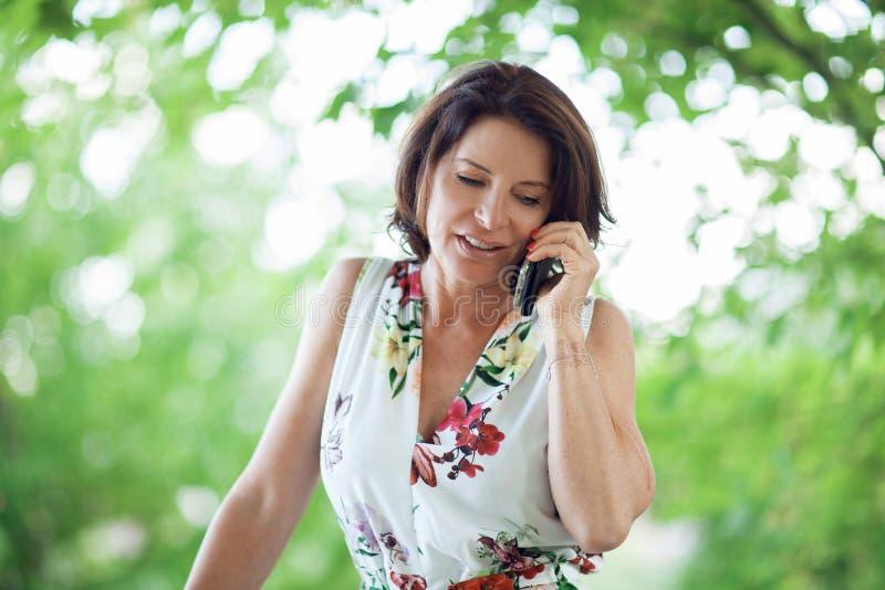 Härlig mellersta ålderkvinna som har en konversation på hennes mobiltelefon arkivbild