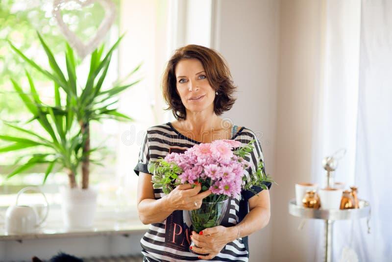 Härlig mellersta ålderkvinna som hem dekorerar med blommor arkivfoto