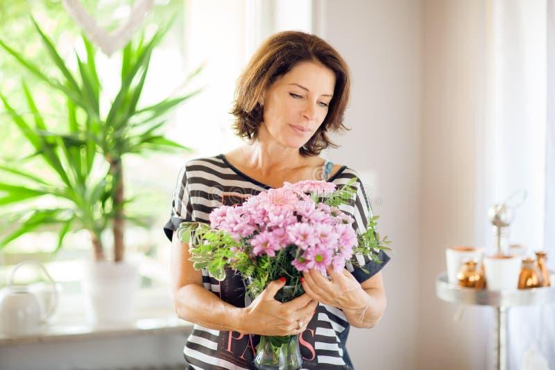 Härlig mellersta ålderkvinna som hem dekorerar med blommor royaltyfria bilder