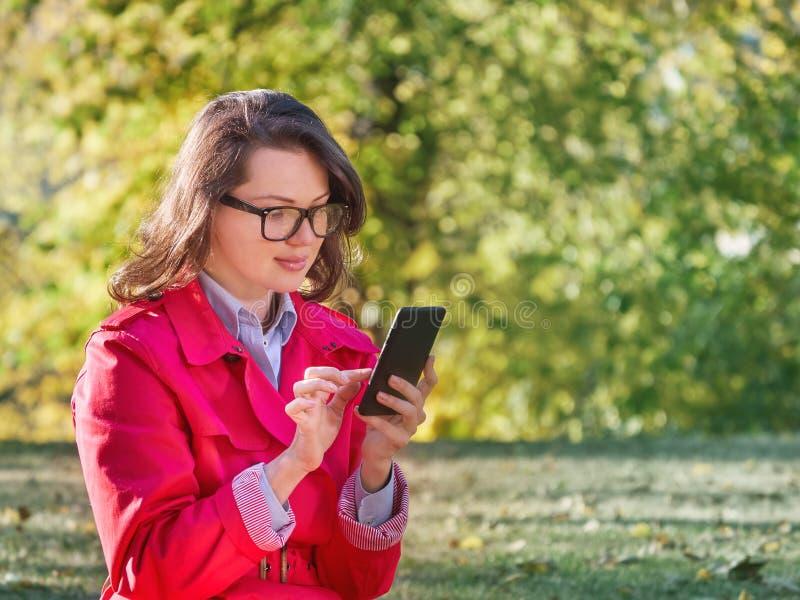 Härlig messaging för ung kvinna på Smart-telefonen royaltyfria foton