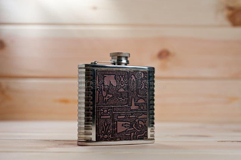 Härlig metallflaska för alkoholdrycker med teckningar i egyptisk stil på en träbakgrund arkivfoto