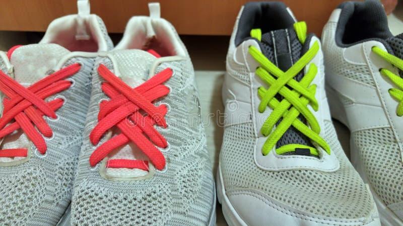 Härlig metod av skosnöreatt binda Färgrika neonrosa färger och gröna skosnöre för limefrukt på vita gymnastikskor arkivbild