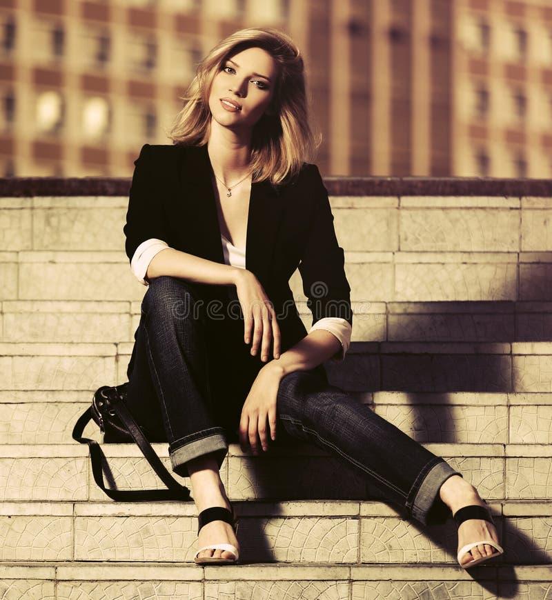 Härlig modeaffärskvinna som sitter på moment royaltyfri bild
