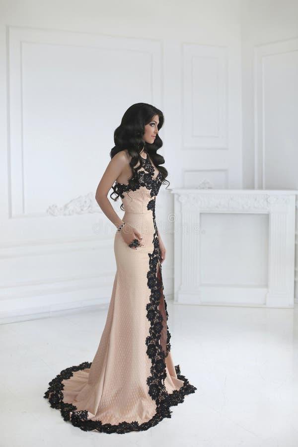 Härlig modebrunettkvinna i elegant klänning med långt krabbt royaltyfri foto
