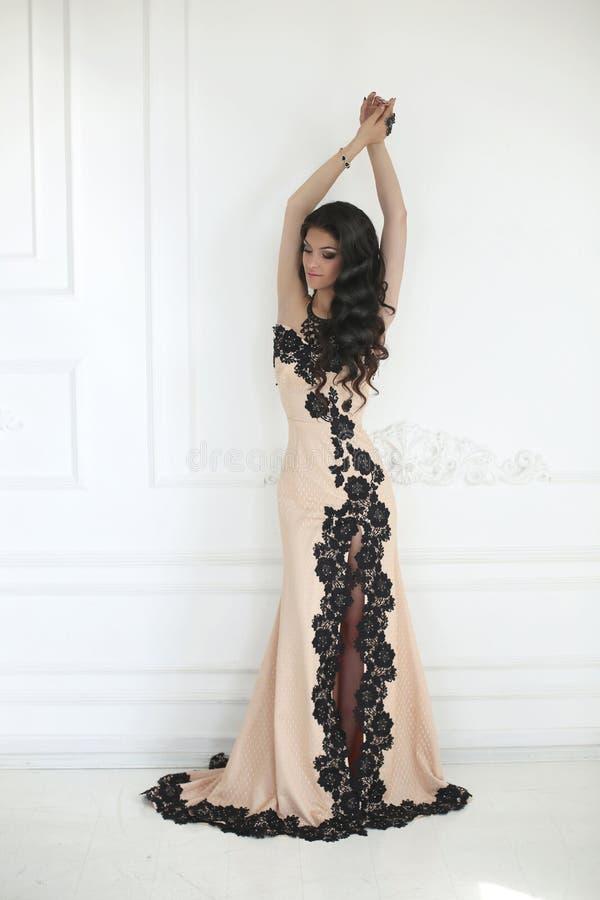 Härlig modebrunettkvinna i elegant klänning med långt krabbt royaltyfri bild